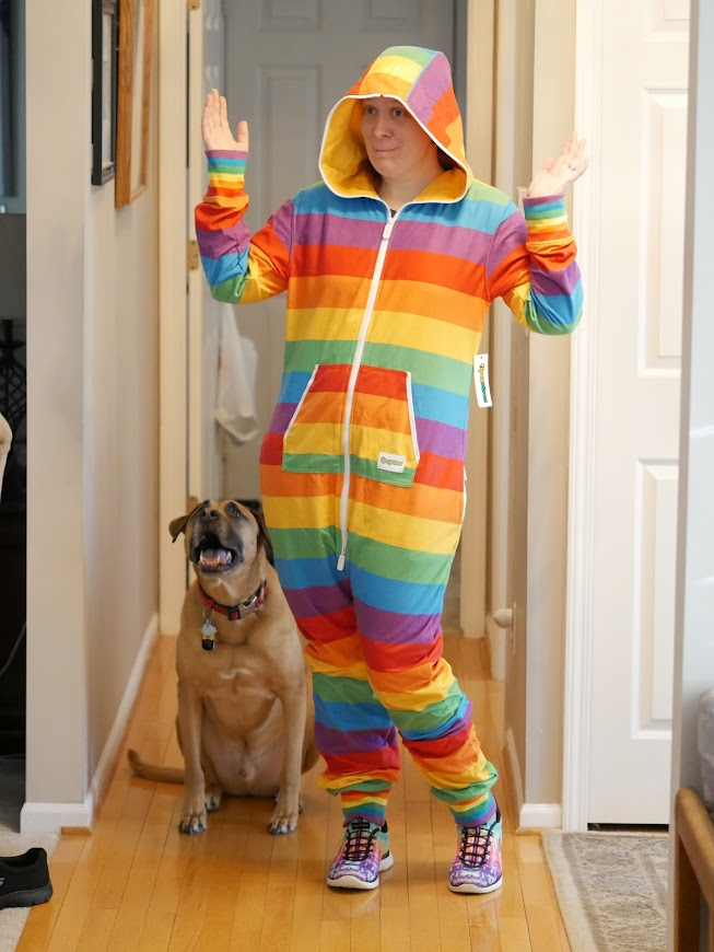 hilary in a rainbow hooded onesie along with her dog Cooper
